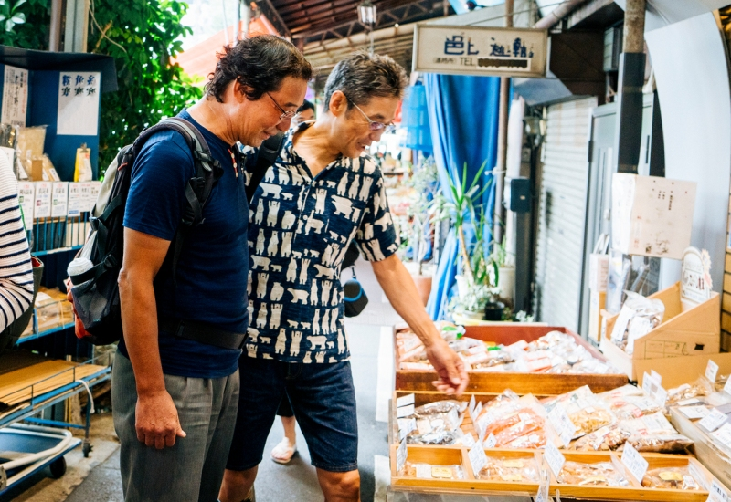 Shoppers look at a market stand's goods during Toshi's Tokyo Airbnb experience Tsukji Asakusa S.S. Tour