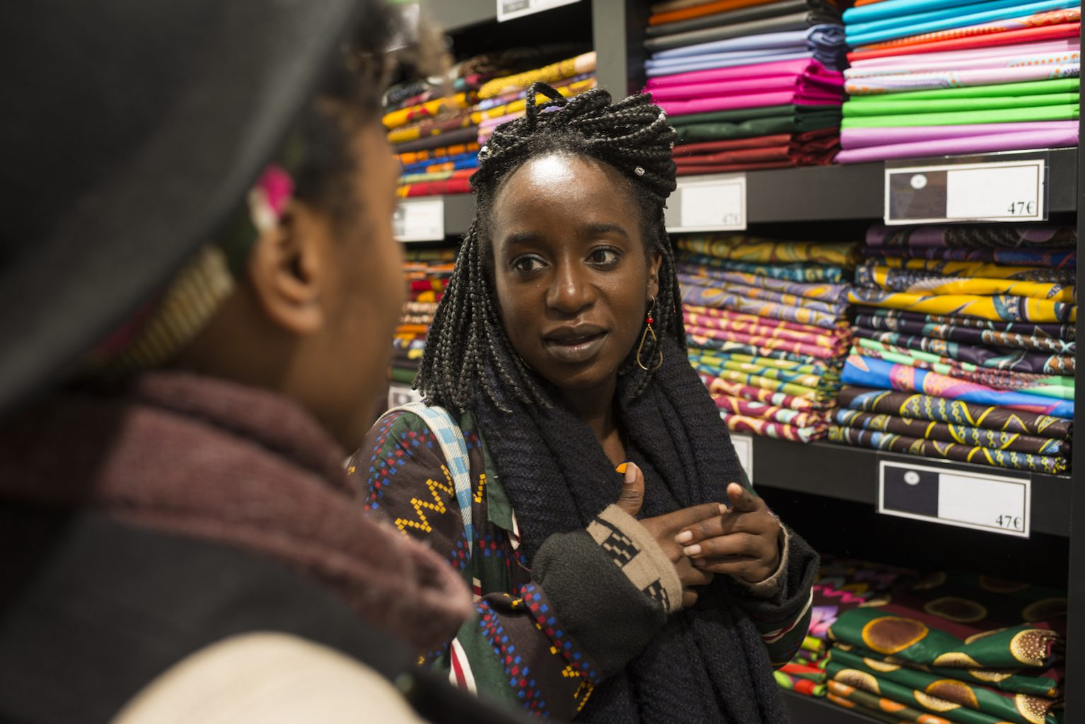 Airbnb experience host Chayet talks to a guest on her Paris Airbnb experience African Fashion in the City