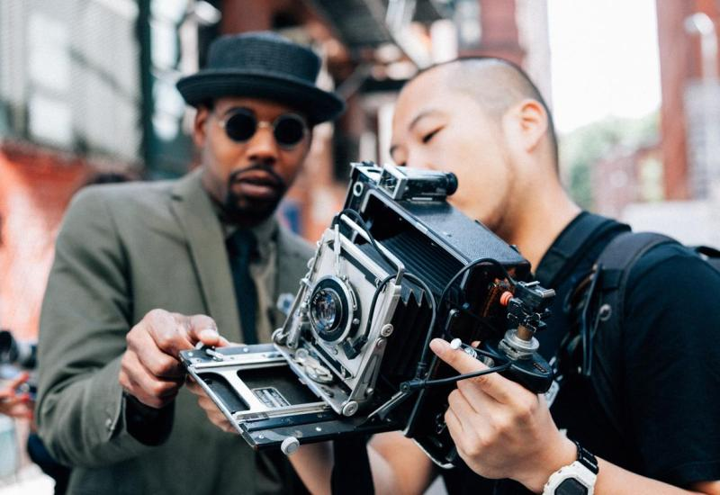 Airbnb experience host Jean Andre shows a guest how to use a Polaroid camera