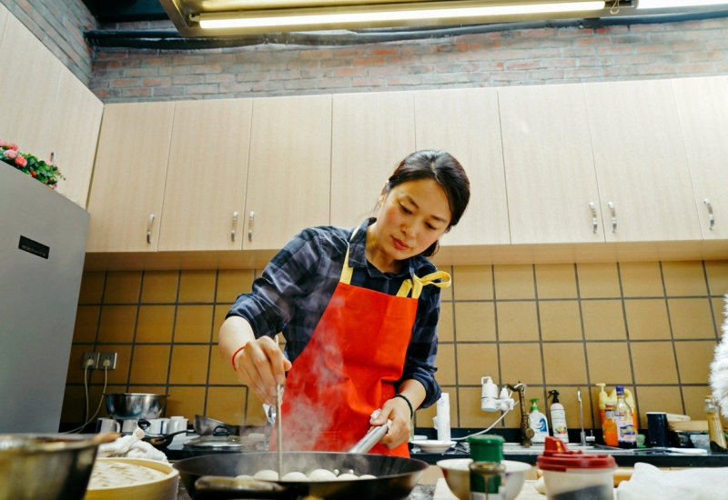 Woman making shanghai soup dumplings in kitchen